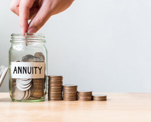 person putting money in a jar labeled annuity